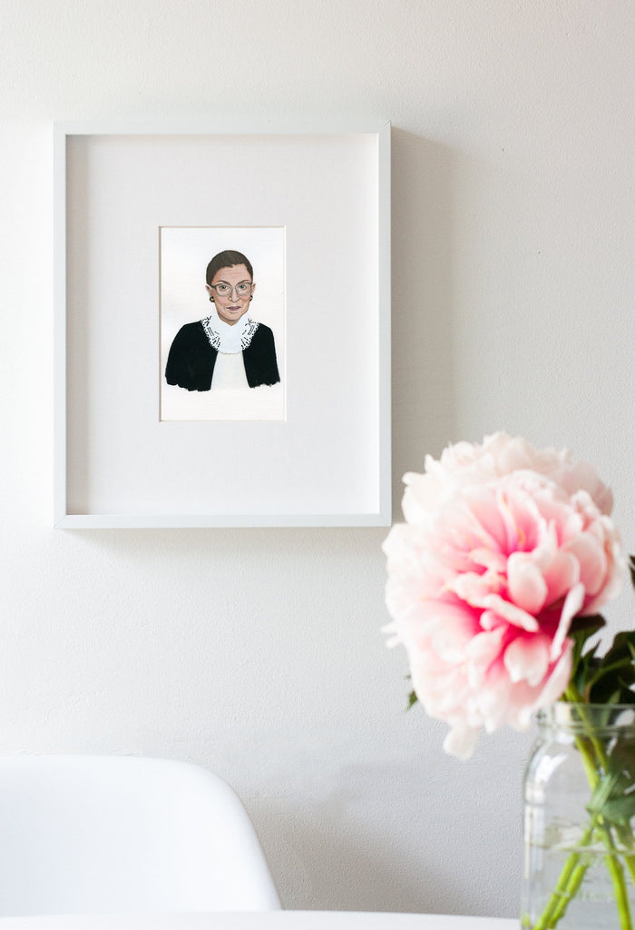 Ruth Bader Ginsberg portrait in gouache by Liz Langley framed in white frame