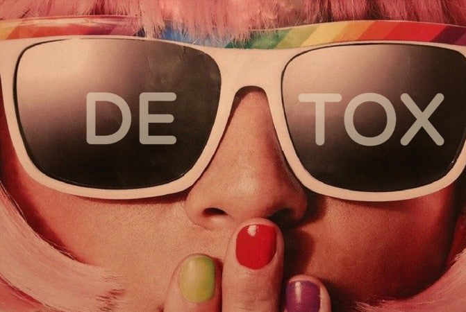 Sia looking gal with pink hair and rainbow glasses and different colored fingernails sporting detox on her sunglasses.