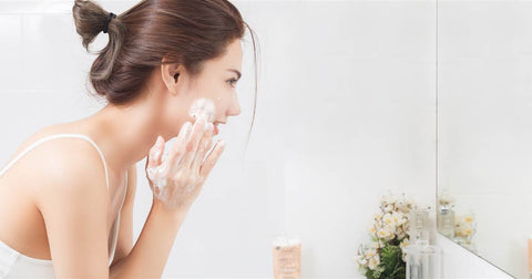 woman washing face before applying The $10 Serum