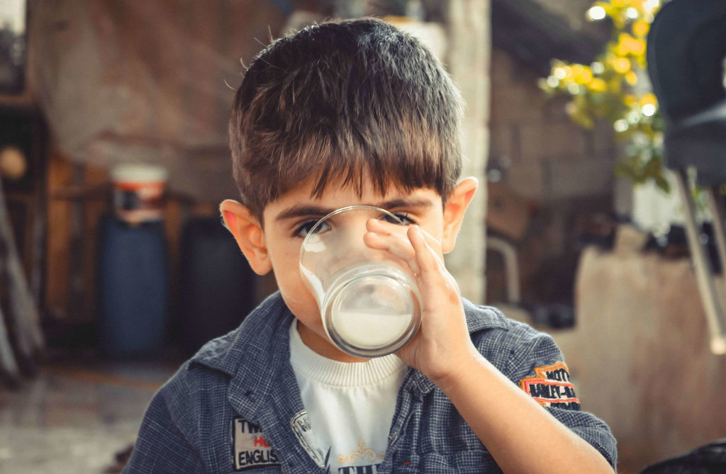 Child drinking milk with CBD oil