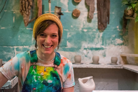 Image of Jennifer Meeker in tie-dye overalls and yellow beanie in her studio