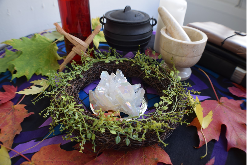 A seasonally appropriate altar with wreath, crystal cluster, cauldron, mortar and pesle, leaves, and books