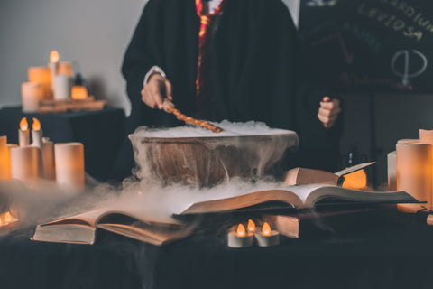image of a boy in wizard robes mixing a smoking potion with books laid before him