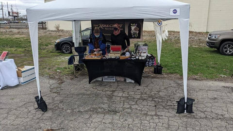 A full view of our setup at the show under a 10x10 tent with weights at each legs and a table set up with our products and a banner with our logo and shop name