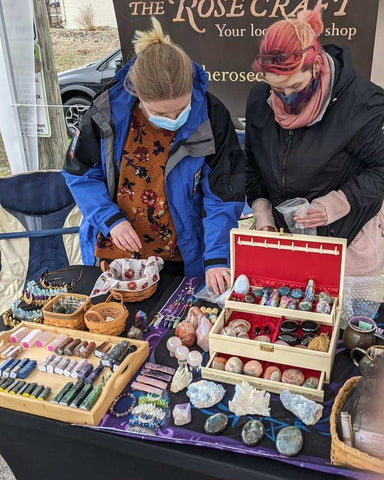 Shopkeeps Cassie and Danielle setting up a table of crystals and products while wearing masks and bundled up for the weather