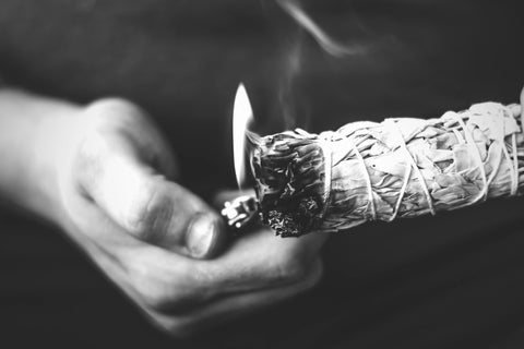 Black and White image of a hand lighting a sage bundle on fire with a lighter
