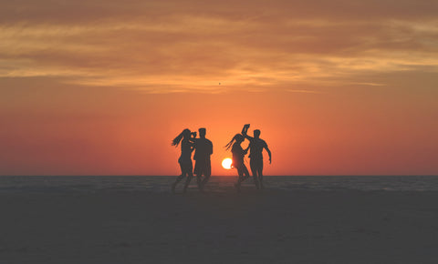 Image four people dancing silhouetted against a sunset