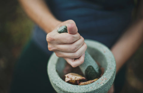 hands crushing herbs with a mortar and pestle