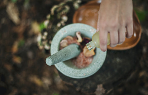 Image of hand pouring oil into a morter and pestle with herbs