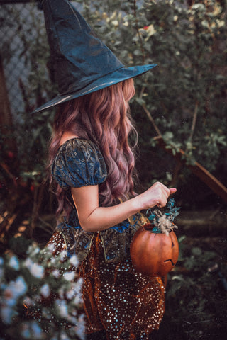Image of a young girl dressed as a witch with a pointy hat
