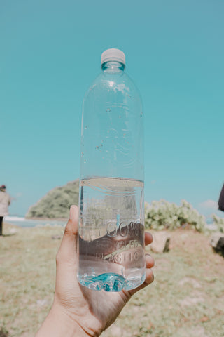 image of a hand holding a waterbottle up to the sky