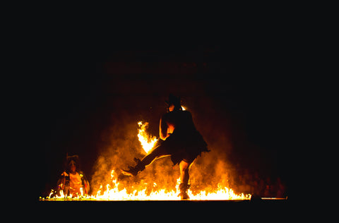 Image of a man dancing silhouetted against a fire
