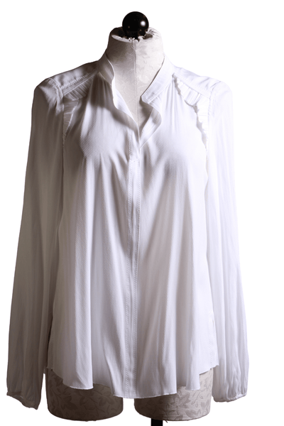 white feminine collarless blouse with small ruffle detail along the collarbone