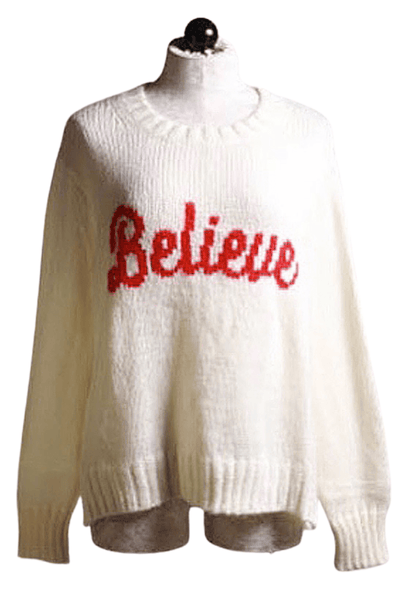 A cream colored pullover sweater with red BELIEVE lettering across the fron