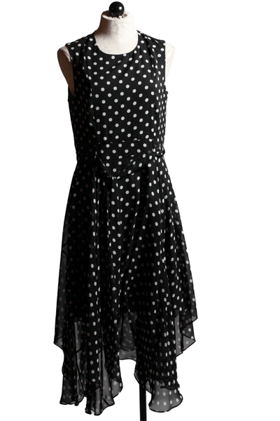 Sleeveless black and white polka dot dress, with tie belted waistband, tiered hem with back ruffle, and back zipper