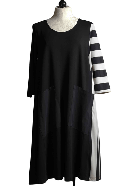 black and white tech fabric dress has two front pockets and the left side has a horizontal striped sleeve and a vertical stripe side panel