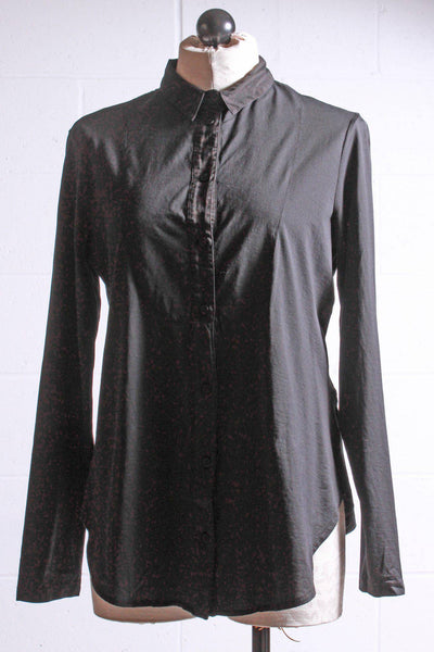 Black blouse with stretch by European Culture with a bib front seaming and partial button placket has a sheen at the top