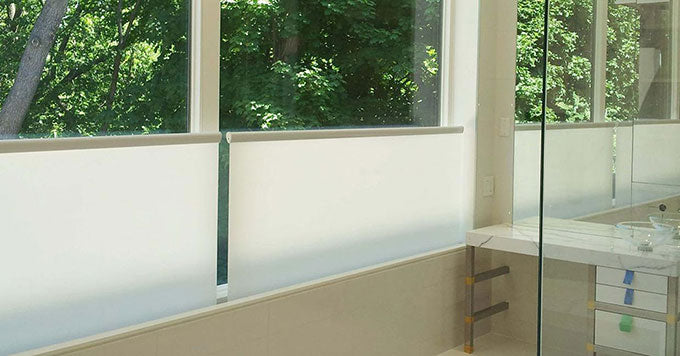 Altex bottom-up shades installed on the windows of a bathroom looking out onto a yard full of green trees