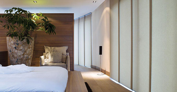Altex panel tracks installed along the vertical floor-to-ceiling windows along the wall of a modern bedroom