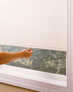 a hand pulling down Elite cellular shades over a window in the day time