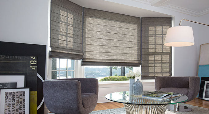 Elite Roman shades installed on the windows of a sunny living room