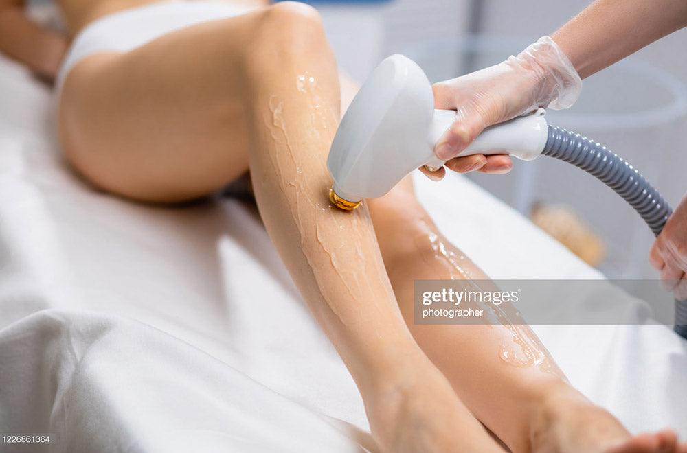 Woman having laser hair removal treatment on her legs