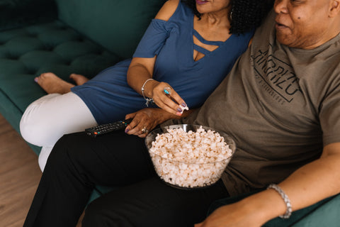 African American couple watching tv eating popcorn