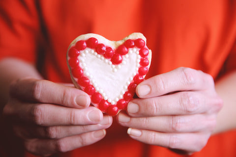 person holding heart shaped cookie