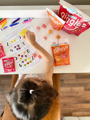 overhead shot of child using yumearth organic chewys to learn