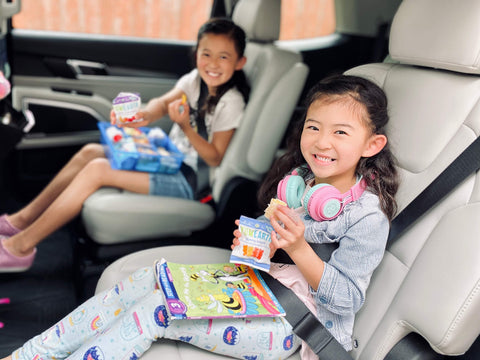 children in car smiling and enjoying yumearth organic candy