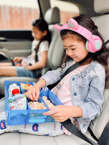 girl in car with lunch snack board