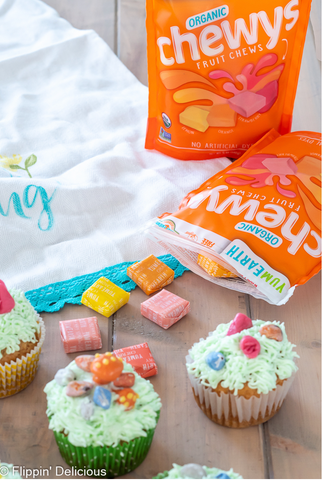 chewy candy spilling out of package with decorated cupcakes