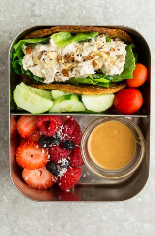 A lunchbox with Chicken Salad sandwich with sliced cucumber and tomatoes on one side and berries with smashed chick peas on other