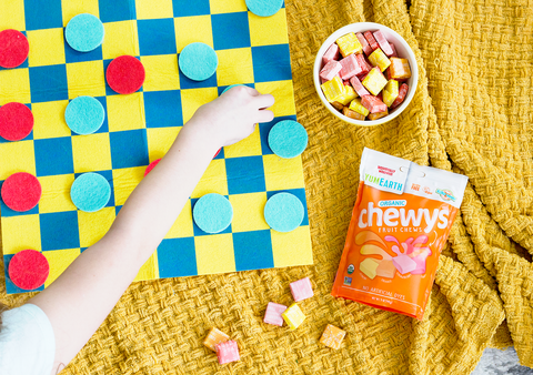child playing checkers with yumearth organic candy featured
