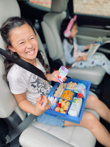 girl smiling in car seat with organic yumearth fruit snacks and snacks for lunch