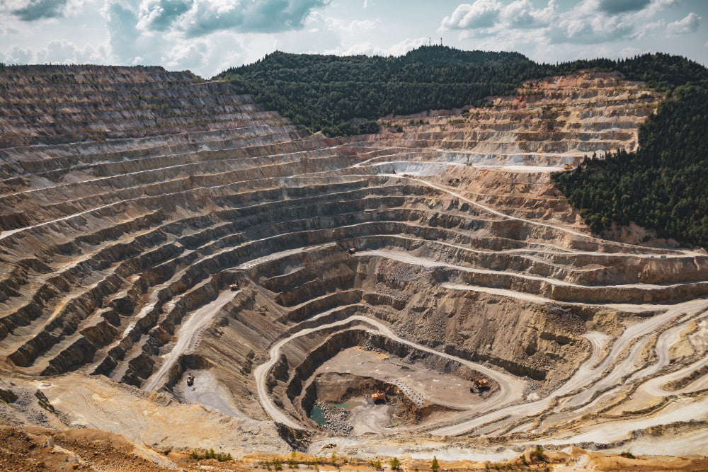Land stripped away by a mining excavation taking place on a mountain, causing significant damage to the environment.