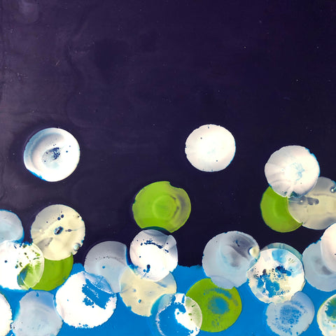 Encaustic painting by Joey M. Robinson featuring circles of white, green and pale blue on a navy background