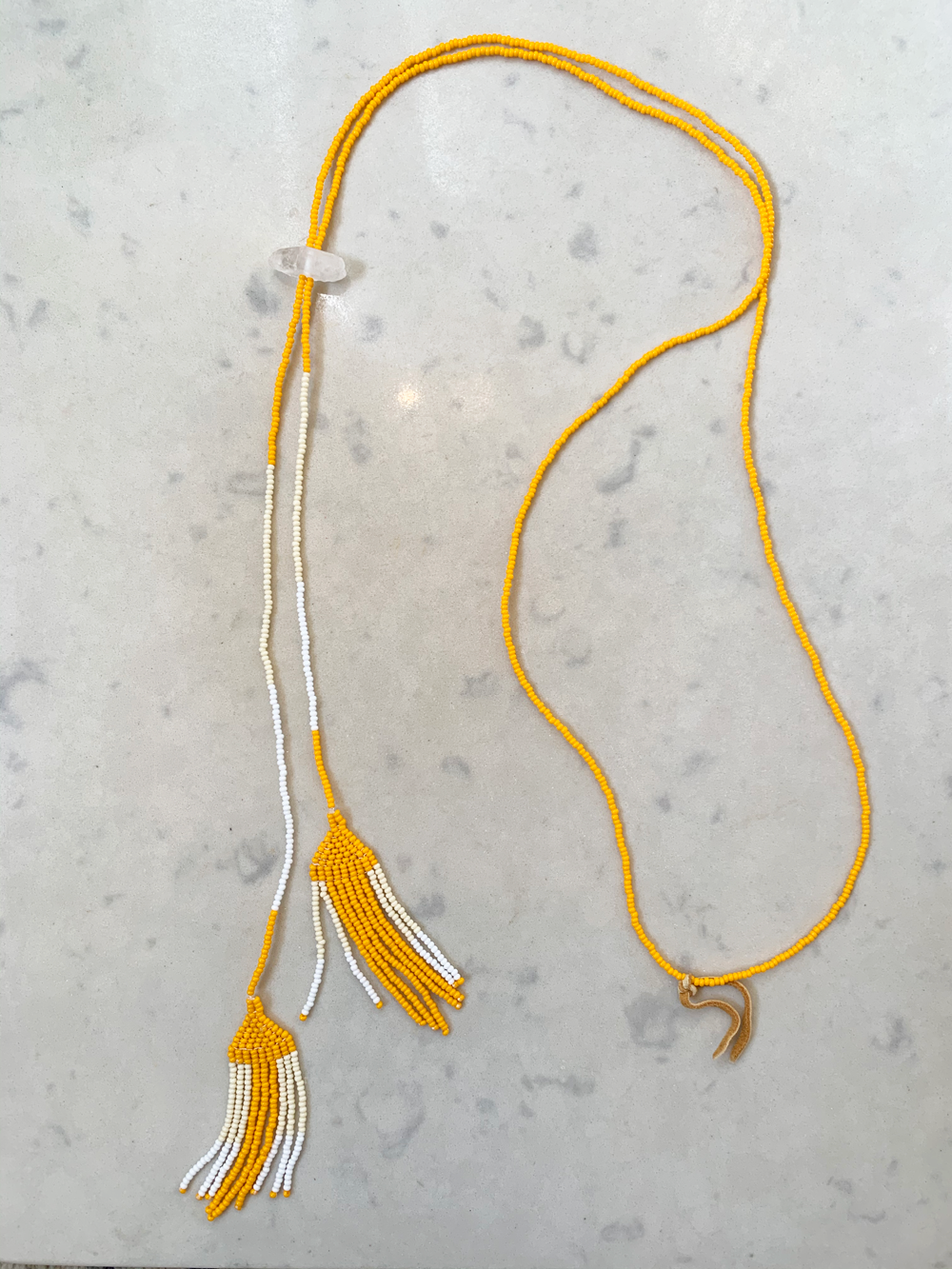 "Hand beaded necklace with yellow/orange and white beads, quartz crystal and vintage leather. Necklace hangs approximately 27"". Pull-on. Styling note: try looping like a lariat!  *Made to order - please allow 1 week + delivery time. Need it faster? Email below and we may be able to accommodate."