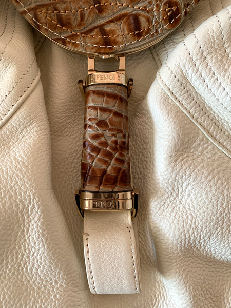 "A true icon, this very gently worn Fendi Spy bag is buttery-soft cream leather with light gold-tone hardware and brown crocodile accents. Change purse and hidden compartment open and function. Change purse pocket has a hole along the seam that could be repaired. Little wear on the outside, two marks as shown in photo. Light wear inside. Measures approximately 17"" wide, by 16"" tall including handles. *Presumed to be authentic but not guaranteed."