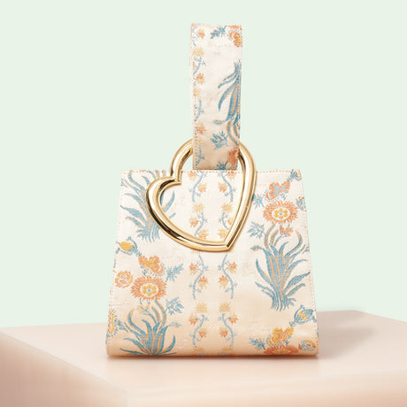 Edie Parker designer handbag Heart Wristlet in cream multi floral satin with loop top handle and metal heart.