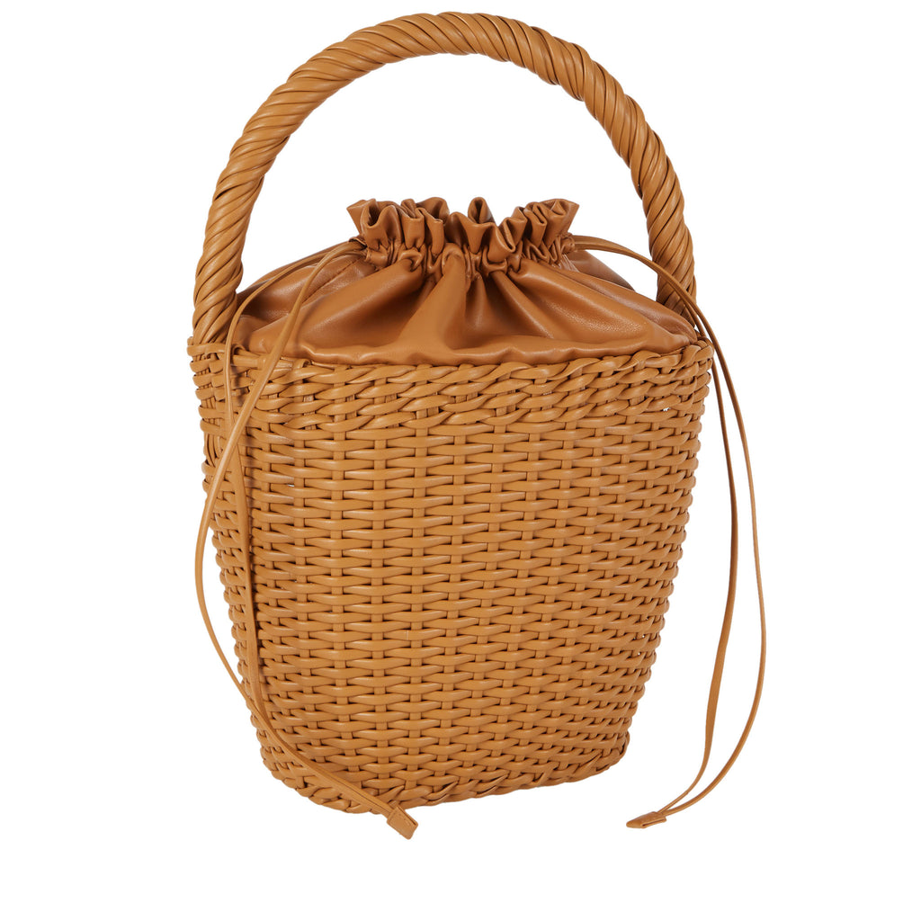 Edie Parker Lily Basket handbag woven straw caramel brown leather drawstring straw twisted handle feature angled view