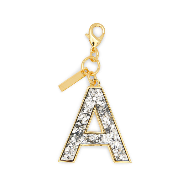 a, Edie Parker designer accessories Initial Charm in Silver Confetti with gold hardware.