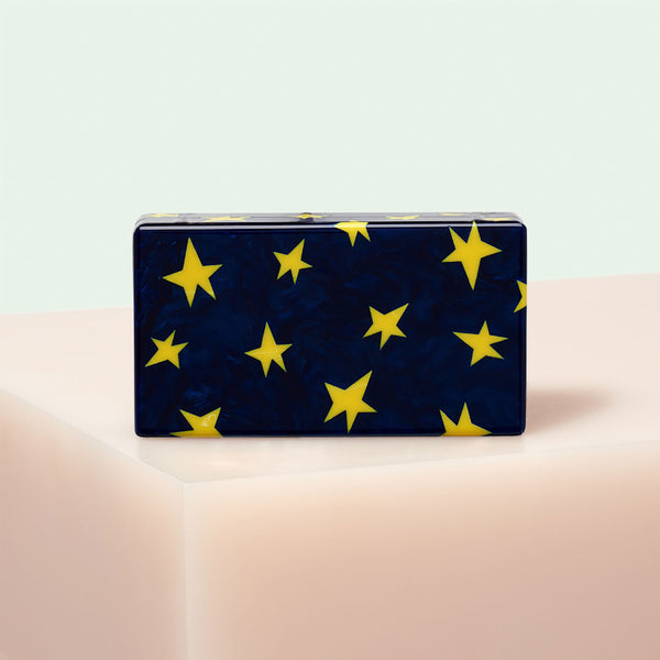 Edie Parker Jean All Over Stars clutch handbag in Navy featuring yellow stars, gold hardware, and gold chain.