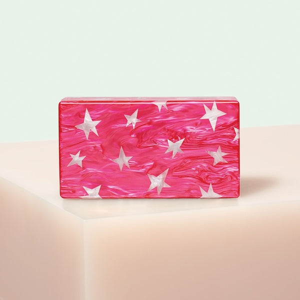 Edie Parker designer Jean Stars clutch handbag in hot pink pearlescent with white stars, gold hardware and gold chain.