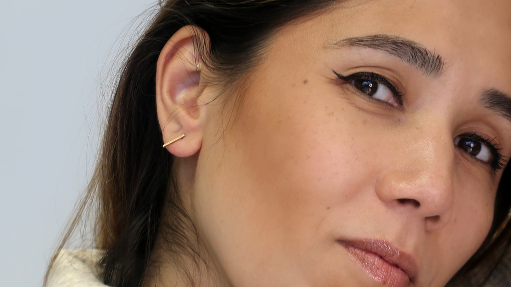 Woman showcasing her ethically-made minimalist Gold Classic Bar studs