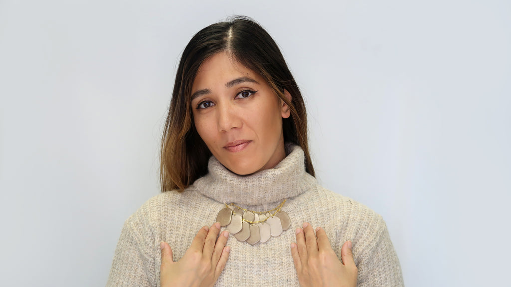 Woman fashionably wears Ethically made Stone treasure necklace on a knitted turtleneck top
