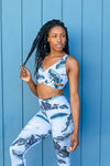 Model Wearing Aura 7 Activewear Tropic Malibu Top posing outdoors against a blue panel wall
