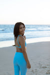 Model wearing Aura 7 Activewear Fresh Air Del Mar Top walking on the beach during sunset