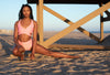 Model wearing Aura 7 Activewear Flower Rigel short doing a yoga pose on the beach in front of a lifeguard tower