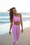 Model wearing Aura 7 Activewear Flower Capella Legging walking on the beach and smiling